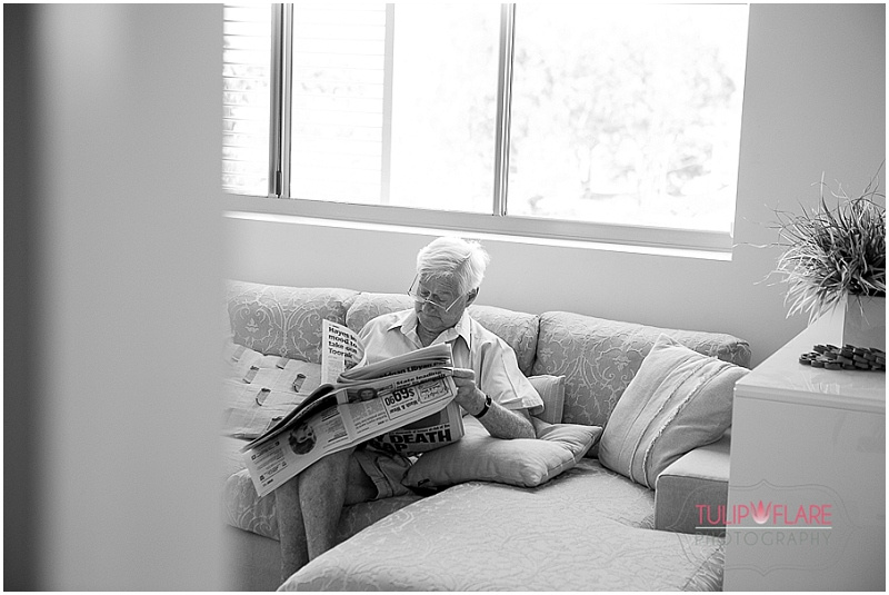 Grand dad reading the paper waiting to go to the wedding