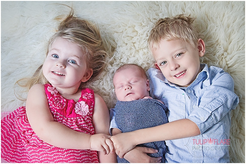 Siblings with their baby brother for a newborn photo session