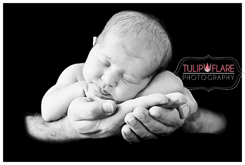 Newborn baby in the hands of her dad on a black background